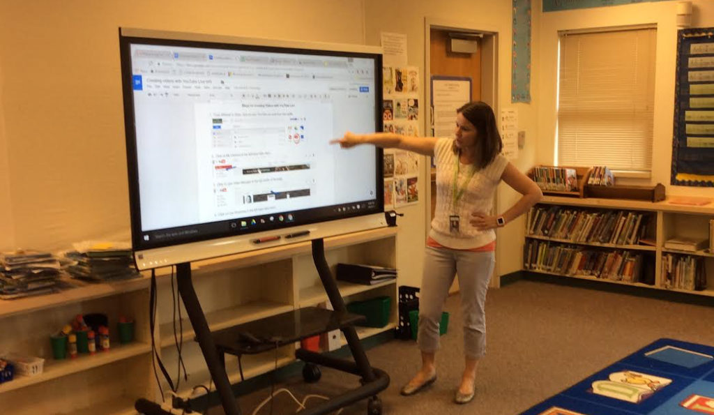 In this picture I am showing teachers where to the reference the steps for recording with YouTube live.